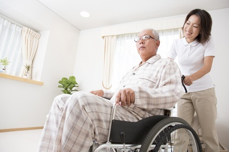 49335786 - caregiver to put the senior man in wheelchair